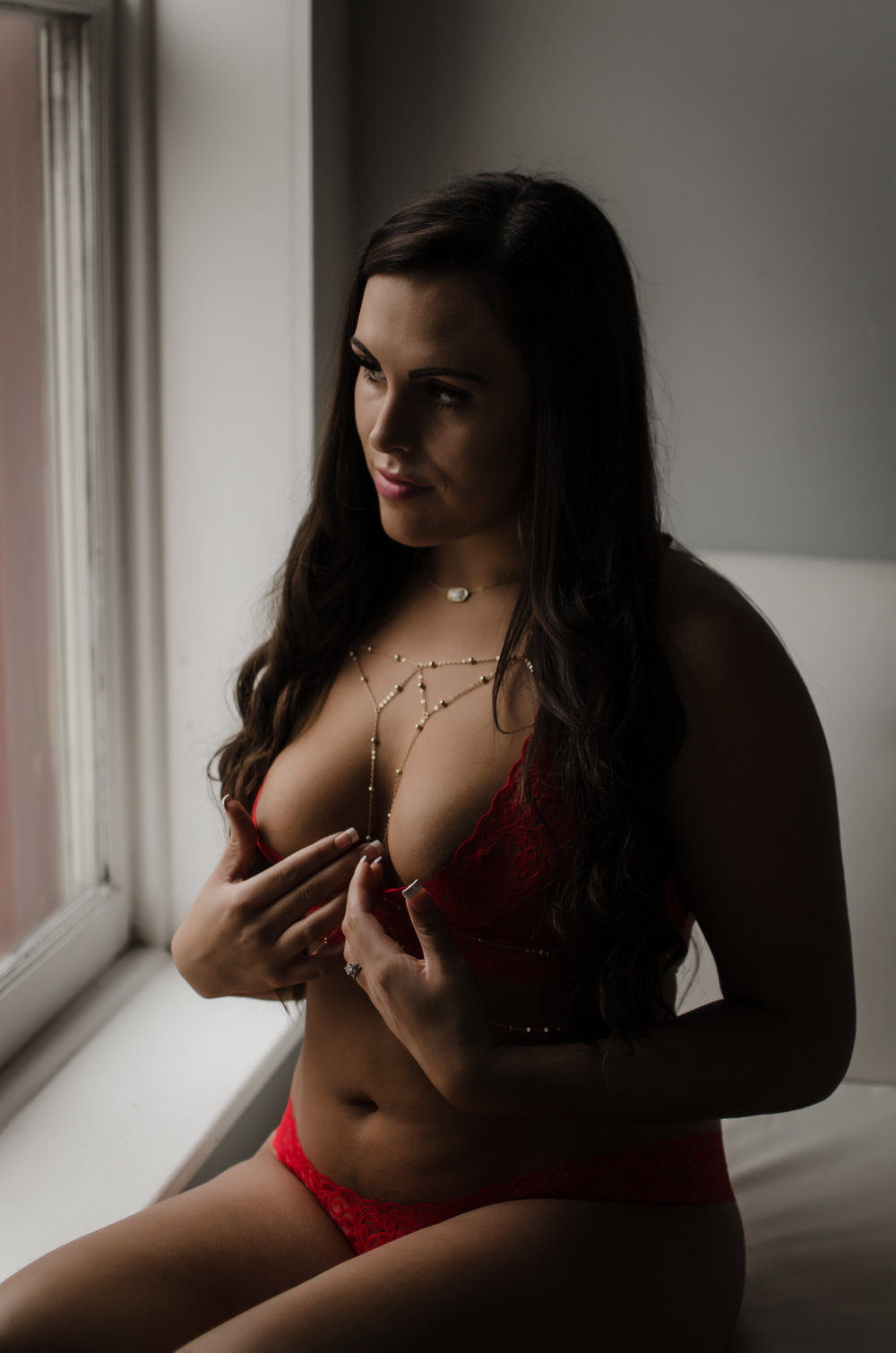 NC boudoir photography experience in belle vue wilmington venue with red lace bra and panties by Victoria Secret  and womens body chain photography by Amandamarie Gillen Photography Wilmington NC photographer sitting by window with natural light touching clevage pose