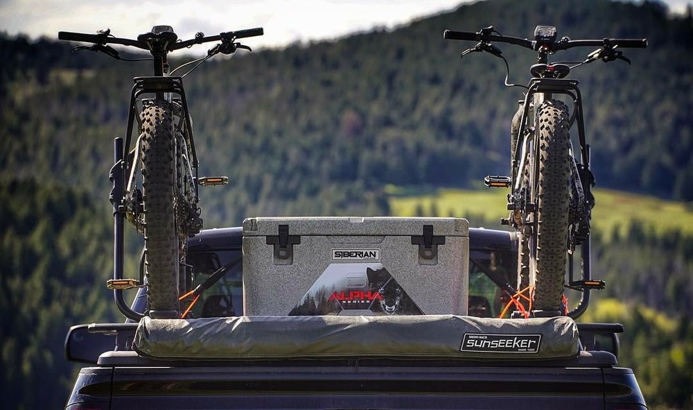 Lifestyle Photo Alpha Pro Series Coolers in the back of a truck with cross country bicycles
