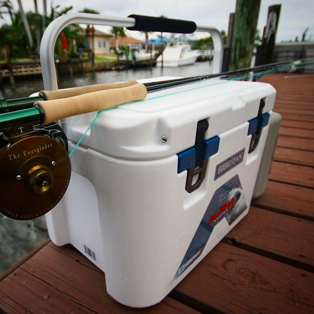 Alpha Pro Series 22 quart white cooler with a fishing rod sitting on a dock