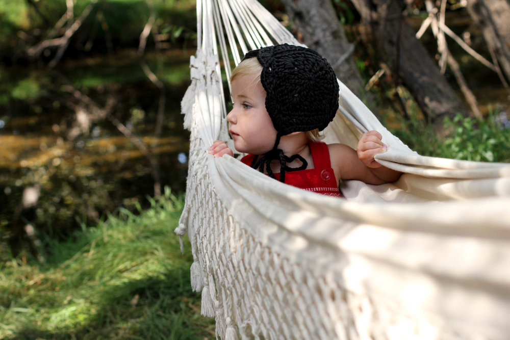 black crochet baby bonnet in hammock