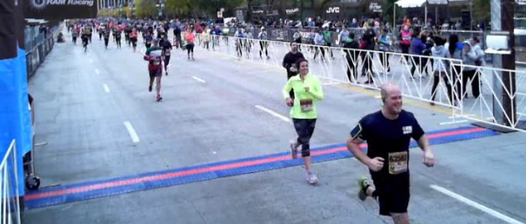 9.3 miles later. I DID IT! (Image description: Me crossing the finish line at the end of a 15k race in Chicago)