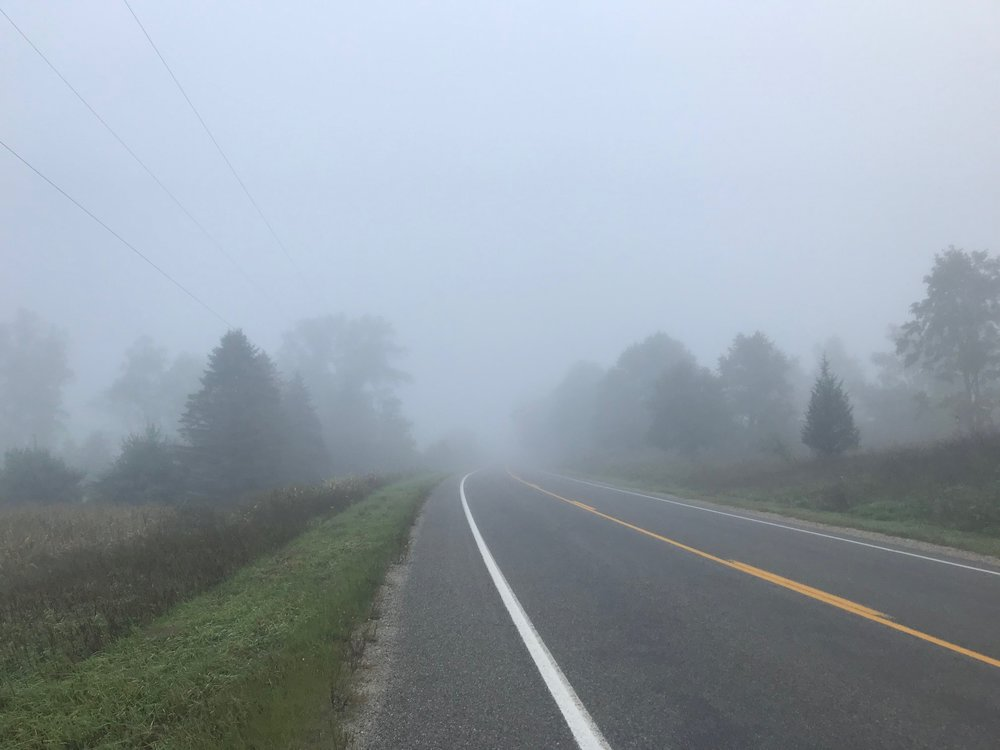Image Description: Rural road on a foggy morning