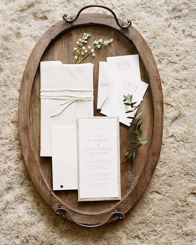 "INVITATION // Inspired by the architecture and textiles found at the venue in Provence, we used natural linen, deckled edge paper, a blind embossed rosette, and leather. Instead of a monogram, we used a finial icon which was seen at the gate when you entered the property. It is always nice looking back at past designs and the wonderful memories that come with it. The invitation set the tone for our wedding and got everyone excited for their adventure to France. We created a booklet that explained to guests the events and why we decided on the location. We are so thankful to Josh for capturing and taking the time to style the invitation suite and details the day after wedding. A special thanks to everyone who was involved in making this wedding possible. // Photo by Josh Gruetzmacher. // Check out Martha Stewart Weddings ""Provence Garden Wedding"" to see more details.  CREATIVE TEAM @yonderdesign @joshgruetz @shannonleahyevents @laetitiac_fleursdatelier @martha_weddings  TAGS #yonderdesign #shannonleahyevents #joshgruetz #luxurywedding #destinationwedding #weddingdesign #provencewedding #frenchwedding #weddinginspiration #marthastewartweddings #eventdesign #letterpress #letterpressinvitation #weddinginvite #luxuryinvites #custominvitations #uniqueinvitation #leatherenvelope #rosette #invitationsuite #wedding"