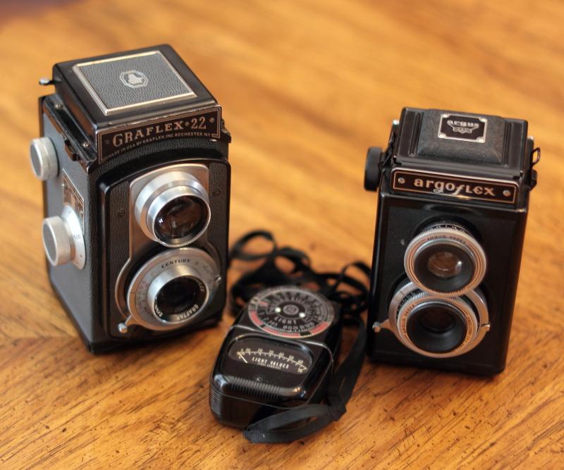 A Graflex 22 Model 200 Twin Lens Reflex camera (ca. 1955), an Argus Argoflex TLR, ca. 1945, and a GE light meter.