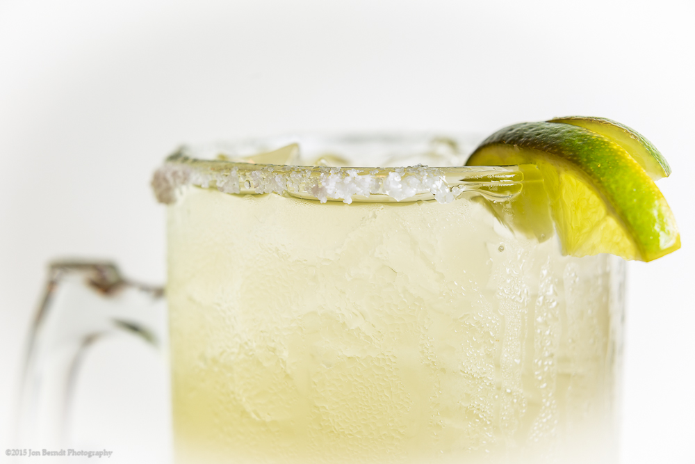 Margarita, with lime, backlit and shot against a white card.
