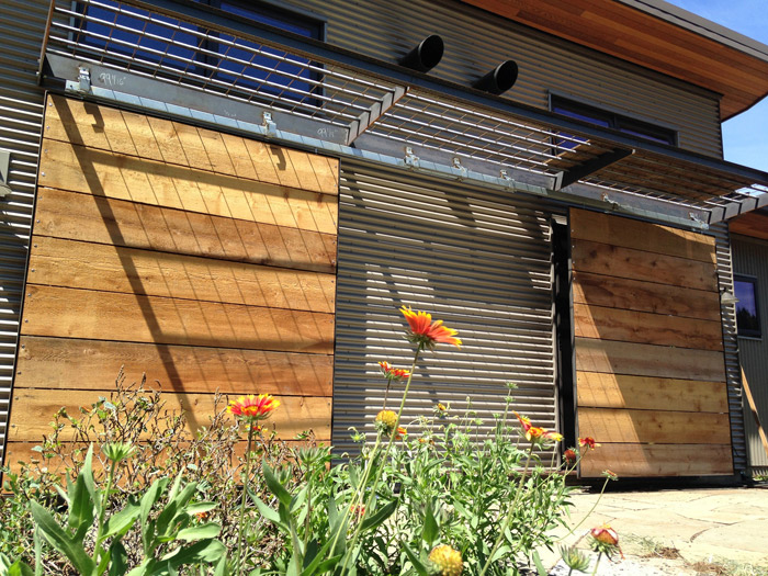 Sliding shutters mitigate the afternoon sun.  Gaps in the reclaimed cedar let the breeze pass through.  The shutters stack between the sliding glass doors when not in use.