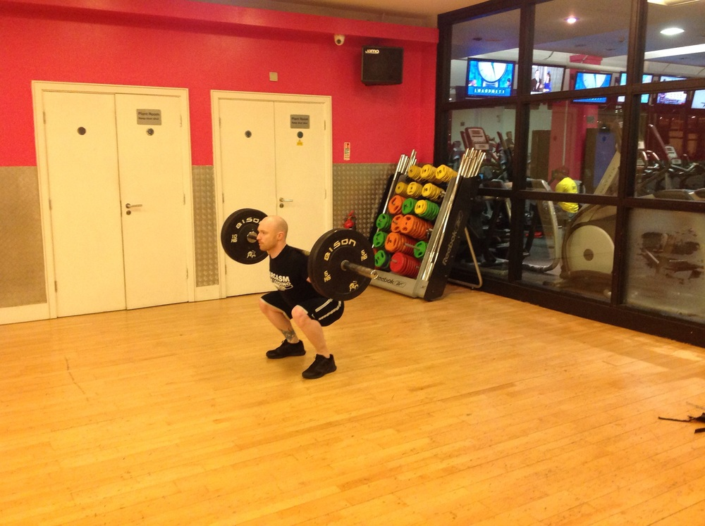 Aaron performing a deep squat, feet slightly more than shoulder width apart, breathing in on way down.