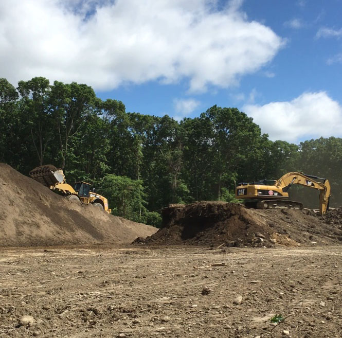 This excavator and loader are screening topsoil to prepare for grading the final design.