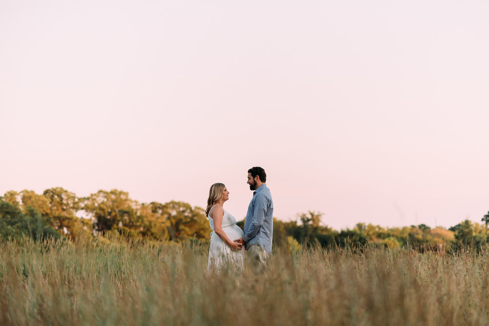 maternity photography pregnant woman in long white dress with husband in field at sunset Baltimore Photographer