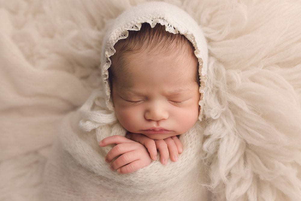 Baltimore Maryland Newborn Photographer Jessica Fenfert baby girl on cream flokati bonnet