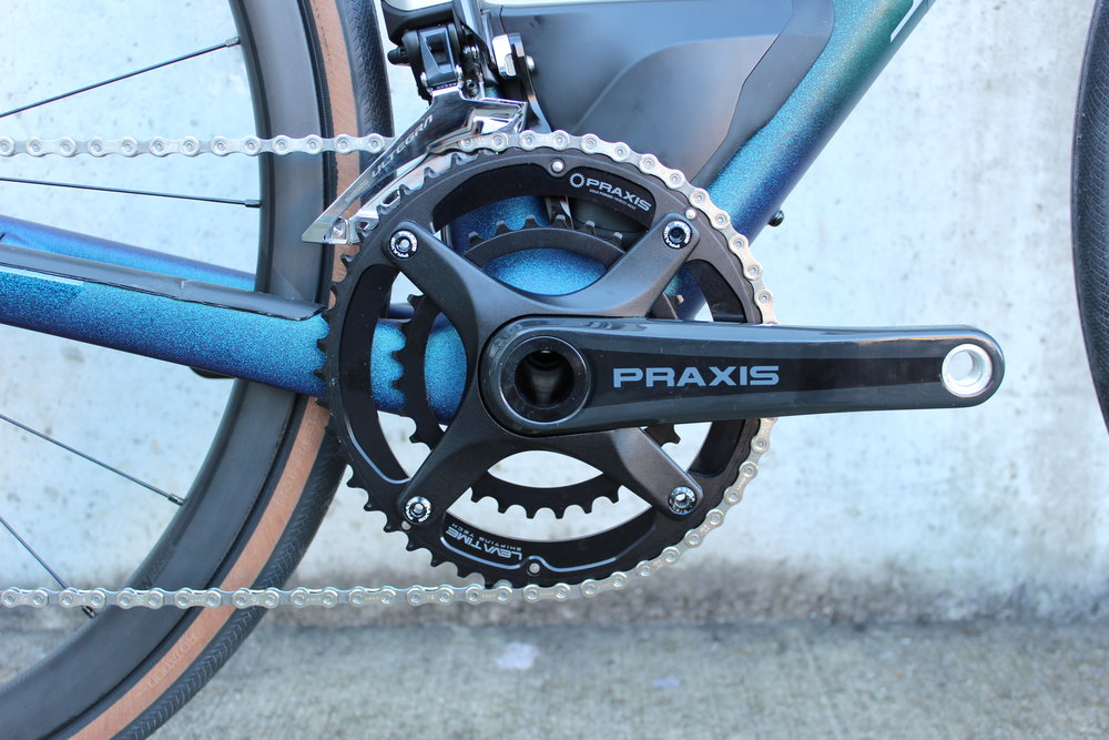 "The Praxis Zayante Carbon Crank comes with ""climb-cruise"" gearing to help you when the terrain gets steeper, but also lets you zip along when you find a gravel highway :)"