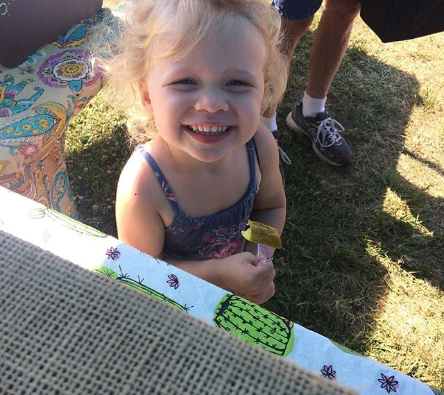 This cutie pie didn't know she liked pickles until she tried on of my homemade ones! This smile is just one of the reasons we love the hampstead farmers market! #farmersmarket #hampsteadmaryland #organic #pickles #produce  #smile