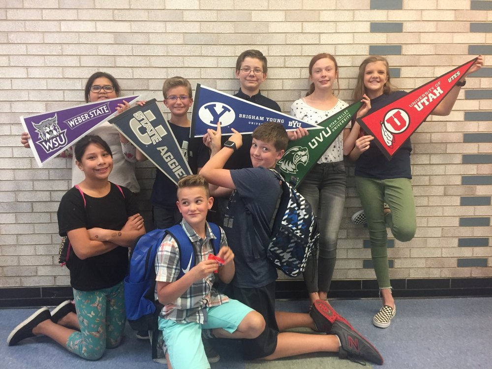 Middle school kids holding college banners