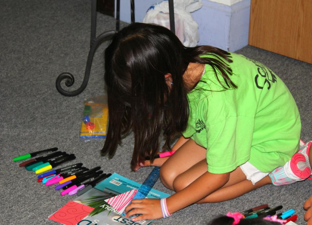 Using her ruler to make a design for her leaf.