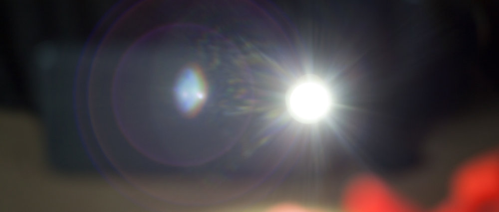IPHONE FLASHLIGHT, STARING POINT SOURCE WITH RAINBOW PARTICLE ABERRATIONS AND MULTIPLE RING FLARES