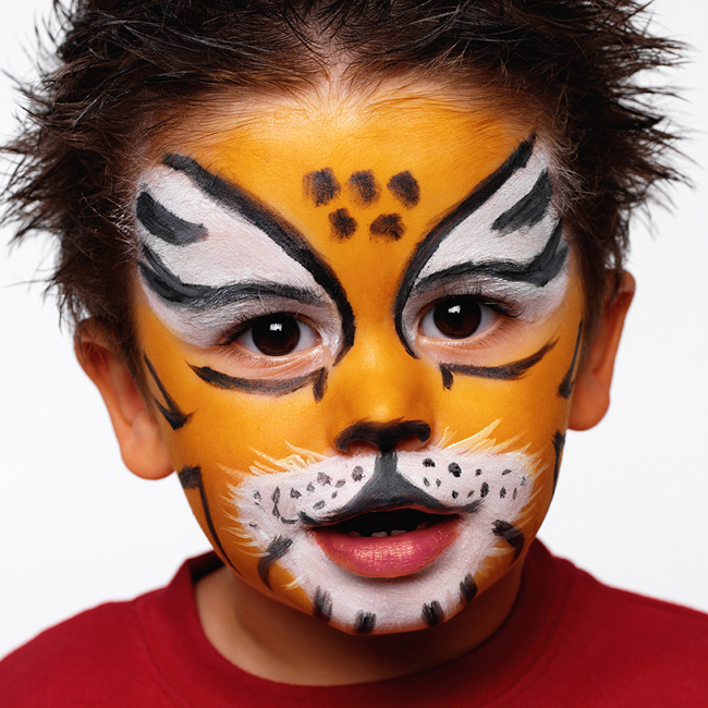 Boy (3-5) with face painted as tiger, close-up, portrait