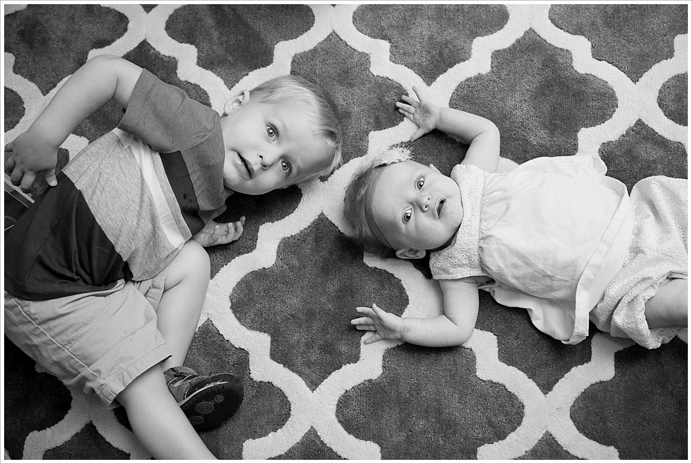 boy and baby sister lay on rug in lifestyle family photography session in Waco, Texas | Jason & Melaina Photography