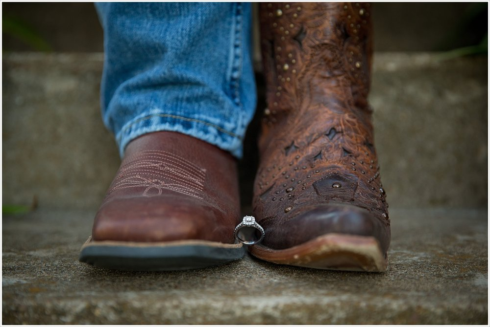 an engagement ring held between a groom and bride's cowboy boots | West, Texas Engagement Portraits | Jason & Melaina Photography