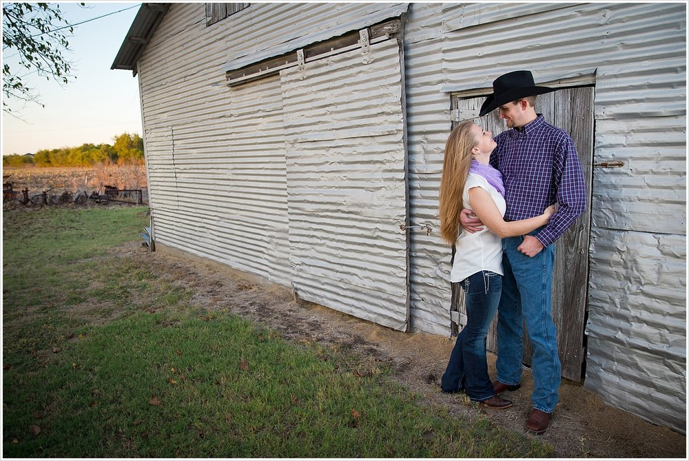 a couple holds each other in front of a steel barn | West, Texas Engagement Portraits | Jason & Melaina Photography