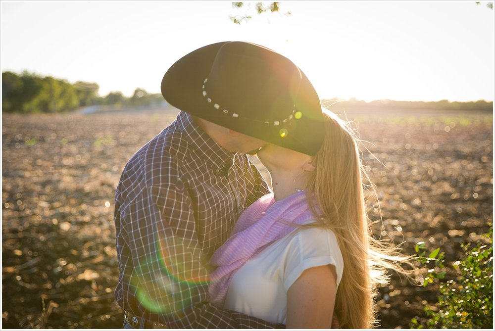 a couple kisses with Texas sunset behind them | West, Texas Engagement Portraits | Jason & Melaina Photography