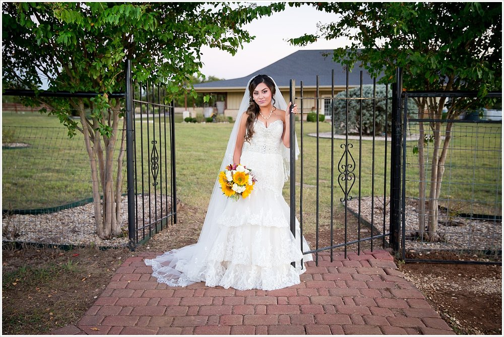 bride by wrought iron fence | Vera Estates in China Springs, Texas | Jason & Melaina Photography