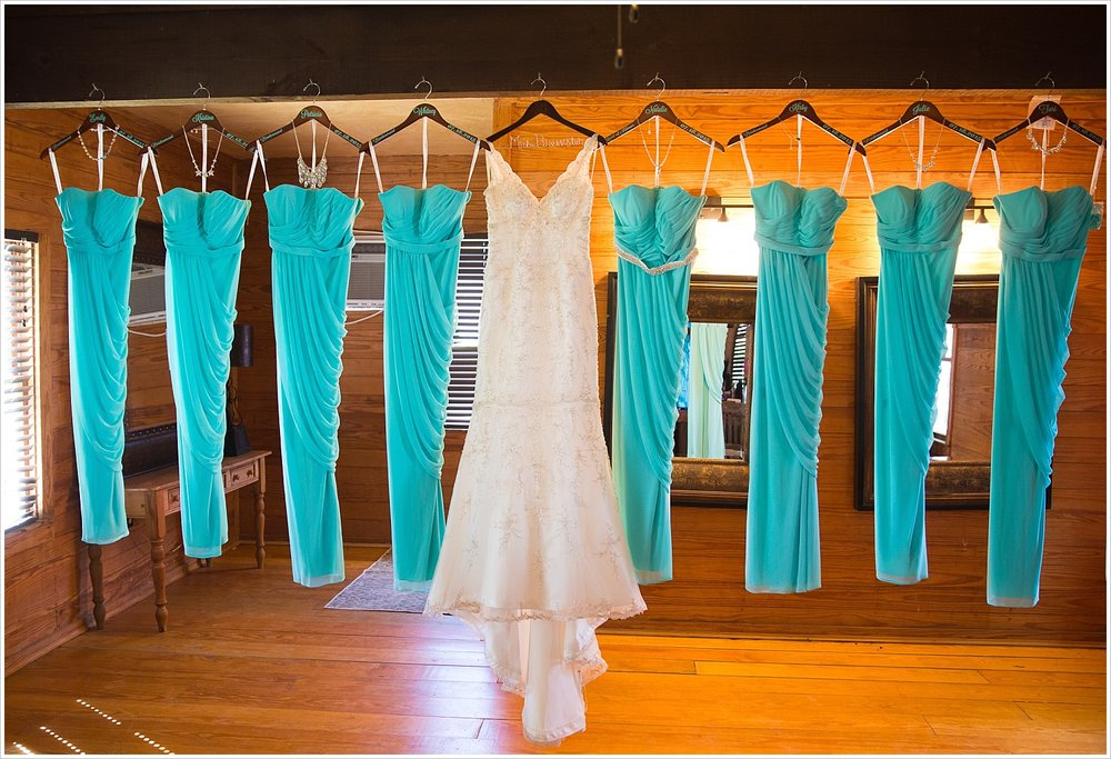 Bridal Gown and Teal Bridesmaids Dress hanging together in bridal getting ready room at Moon River Ranch