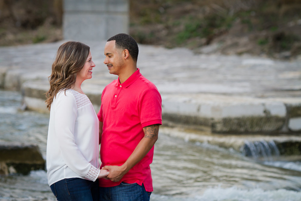 Couple looks into one another's eyes beside flowing creek in Belton, Texas