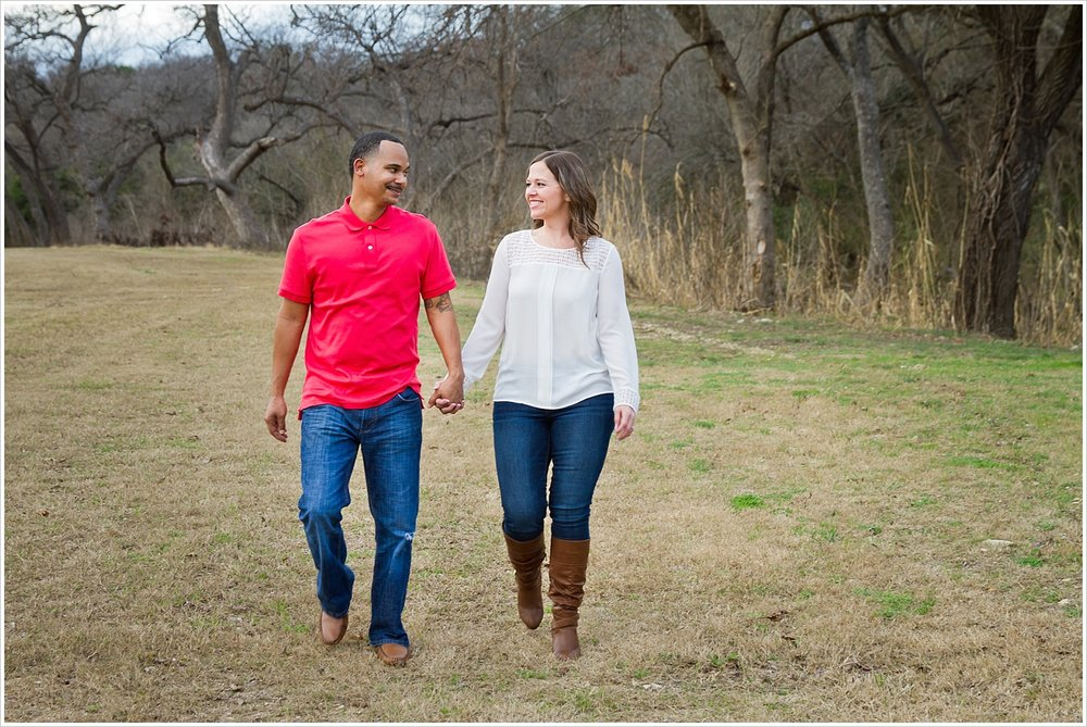 Couple walk hand-in-hand in field in Belton Texas