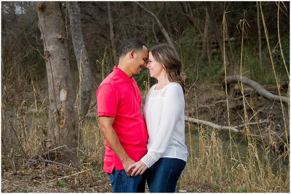 Couple looks into one another's eyes beside creek in Belton, Texas