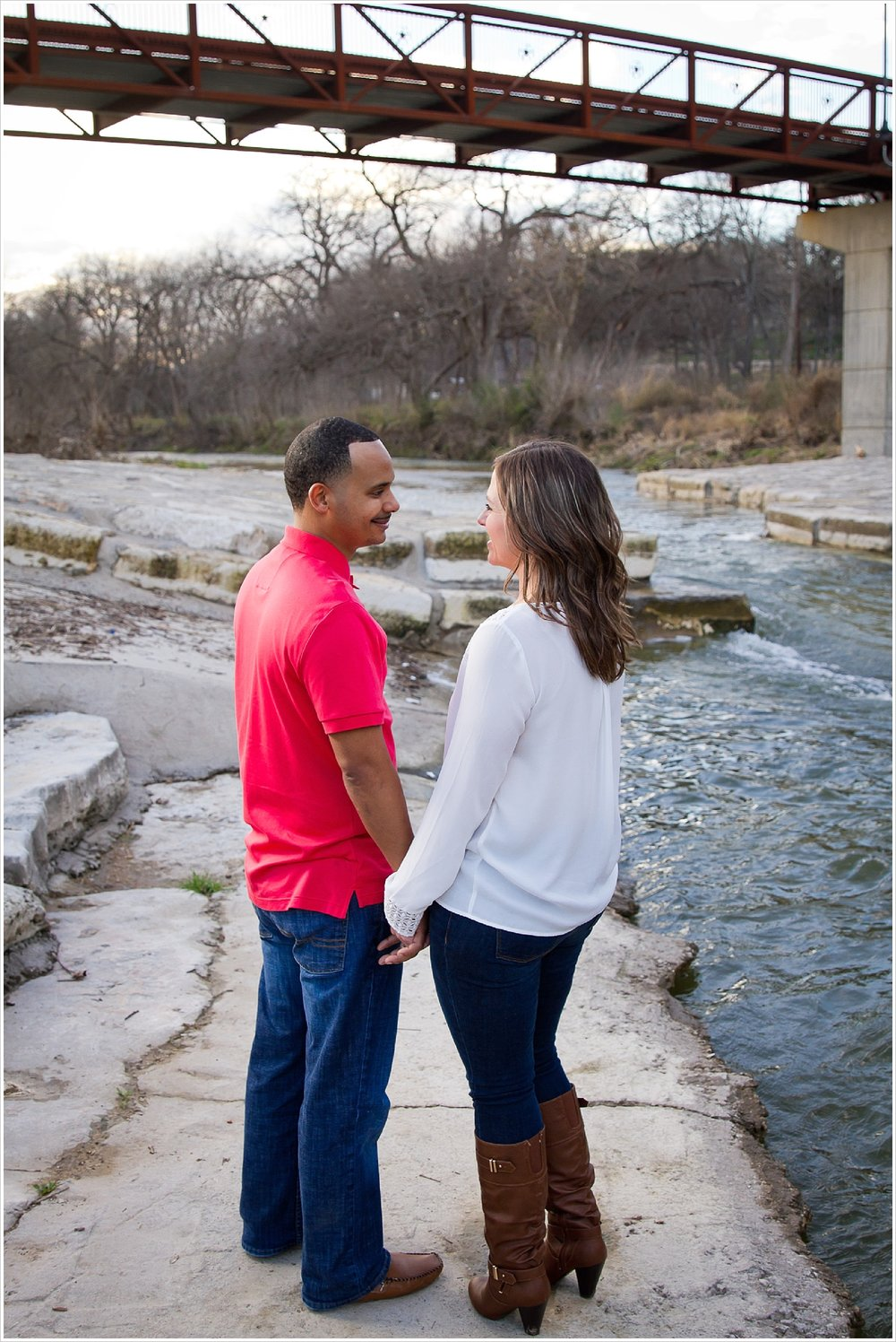 Couple looks into each other's eyes during engagement session at Nolan Creek in Belton, Texas