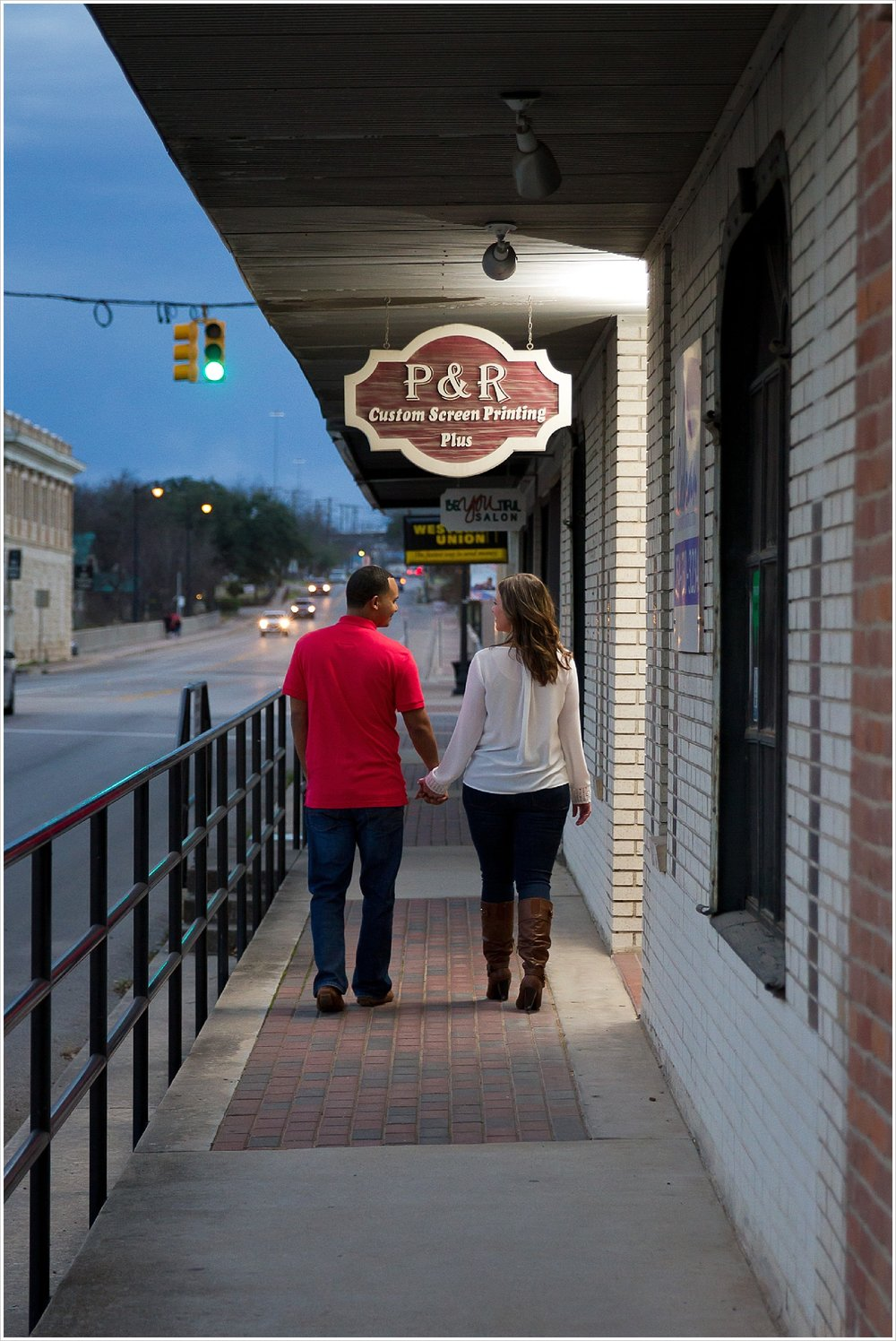 Couple walks hand-in-hand on sidewalk in downtown Belton, Texas
