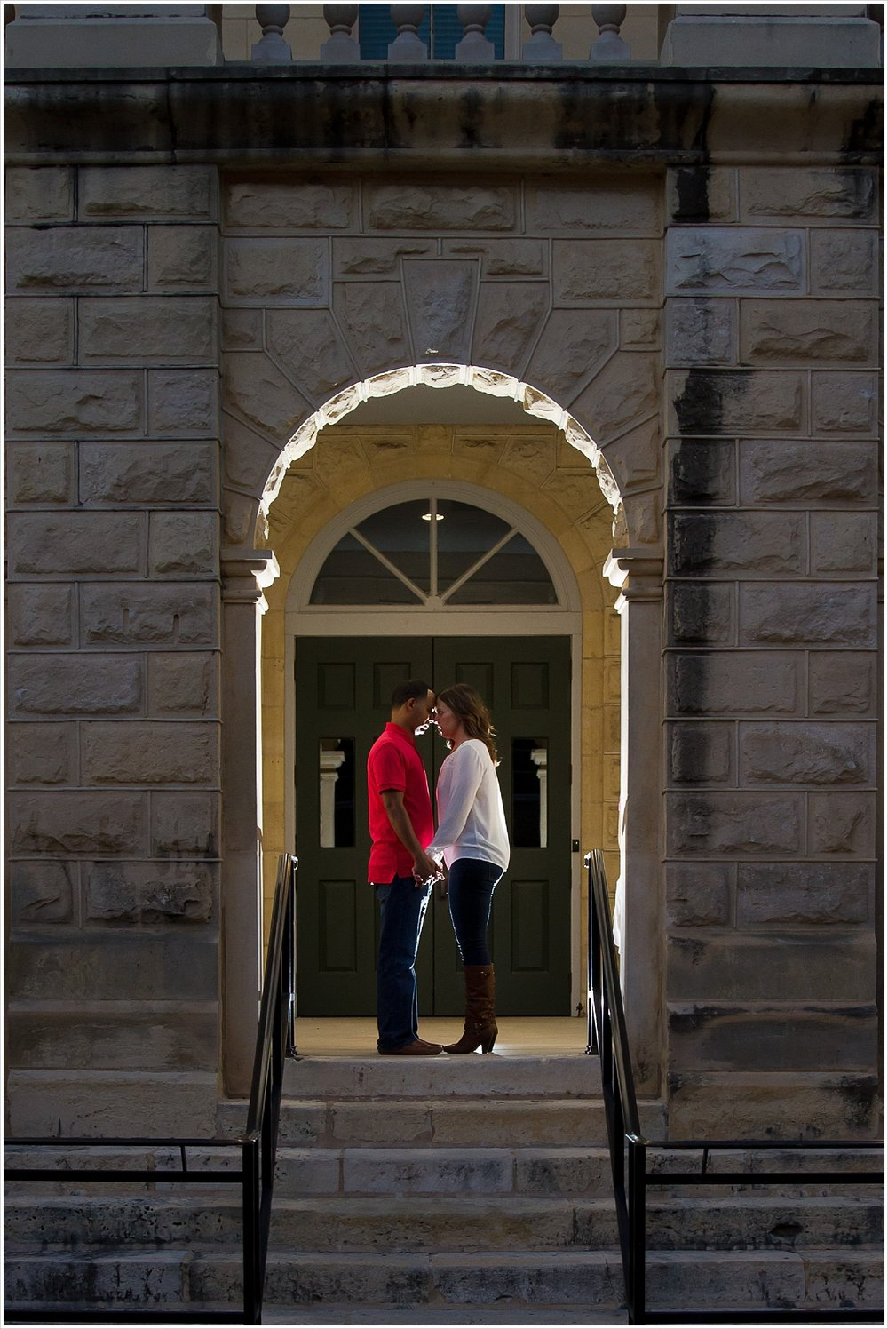 Couple poses in archway of courthouse, backlit by flash, in downtown Belton, Texas