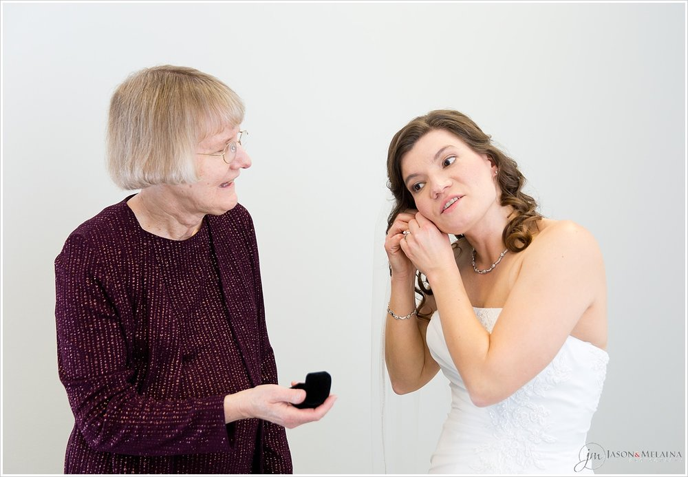 Bride putting on groom's grandmother's earrings