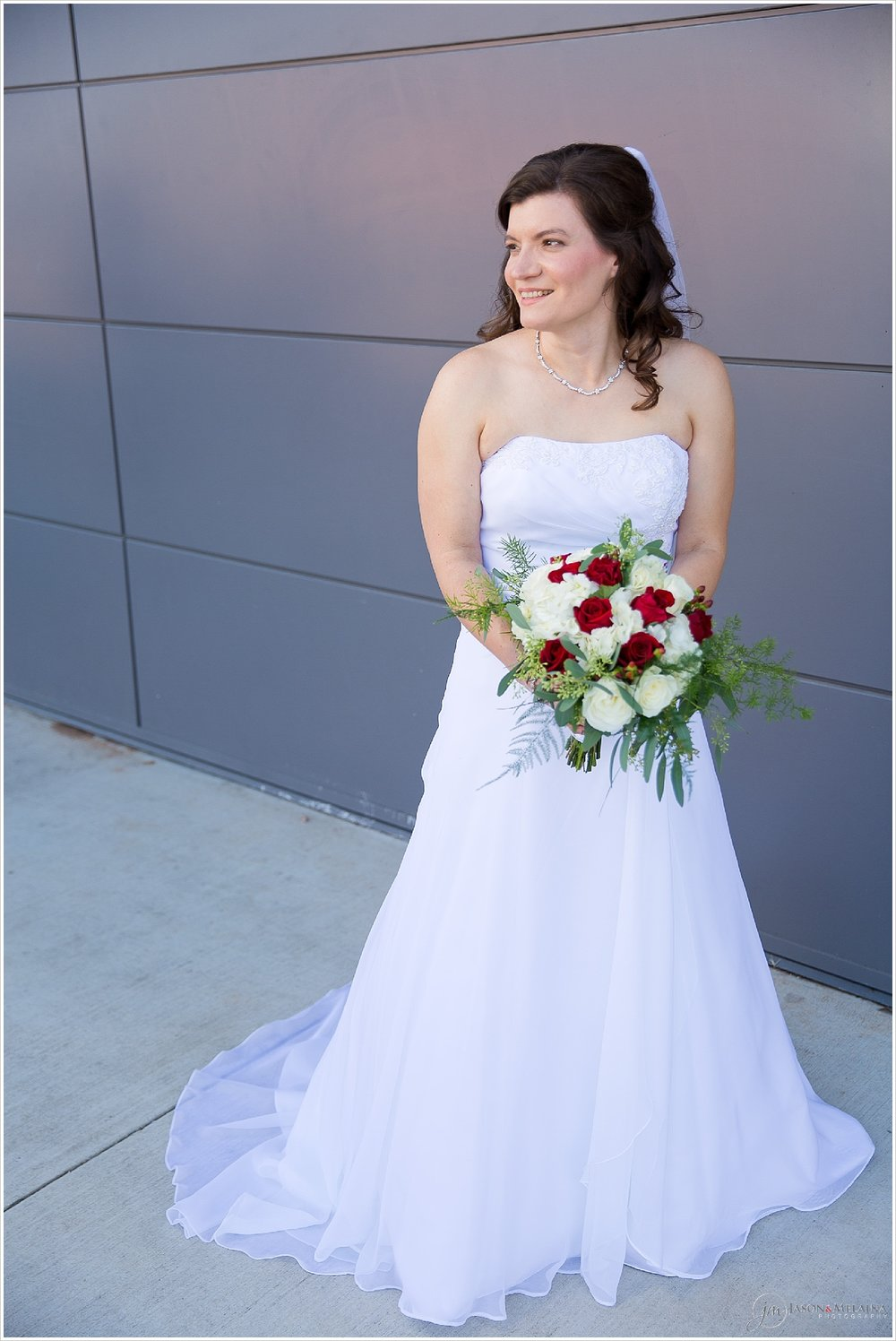 Bride with red and white rose bouquet poses outside Antioch Community Church in Waco, Texas