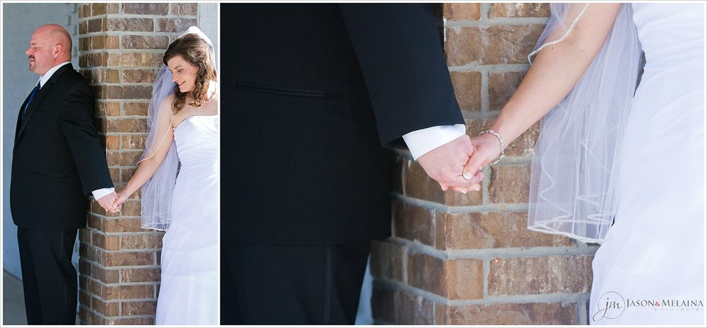 "Close up on bride and groom holding hands during ""first touch"" before wedding ceremony"