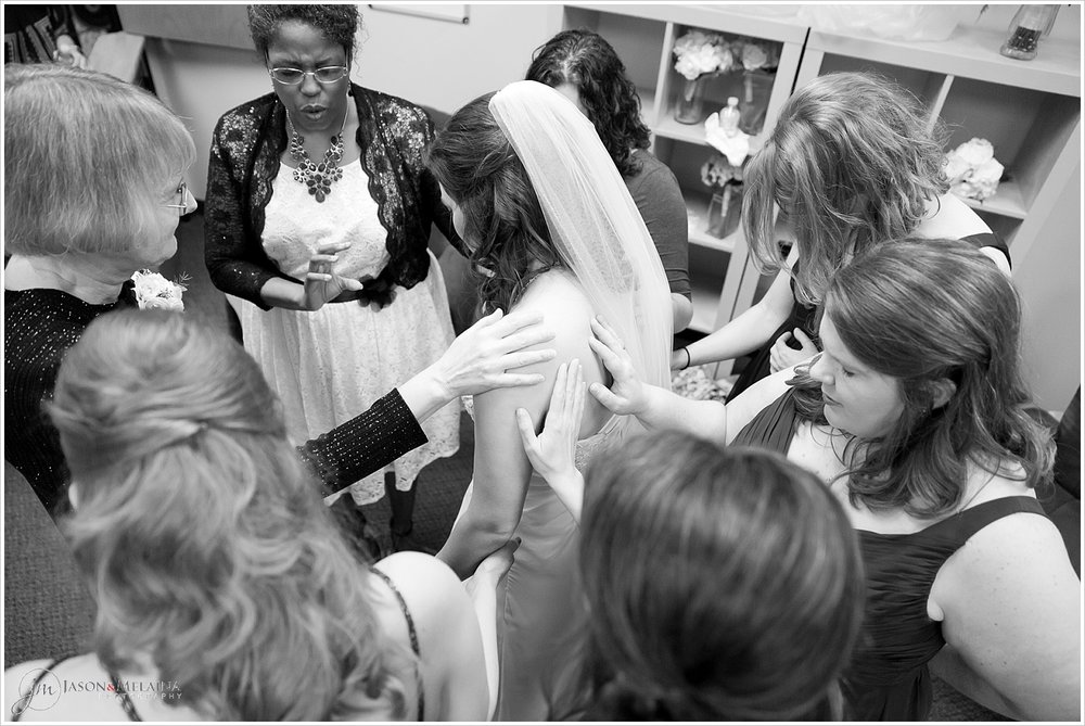 Bridal party prays over bride prior to ceremony, Antioch Community Church in Waco, Texas