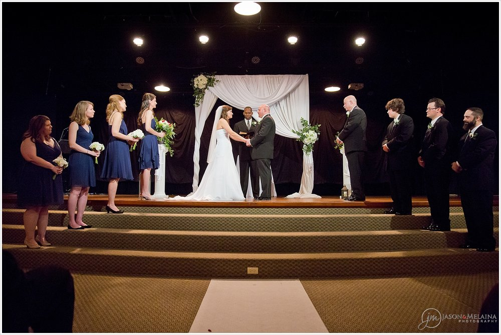 Wedding Ceremony with bridesmaids in navy dresses and groomsmen in black tuxes