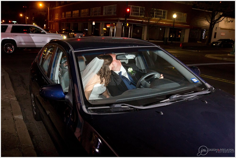 Bride and groom kiss inside their getaway car outside the reception