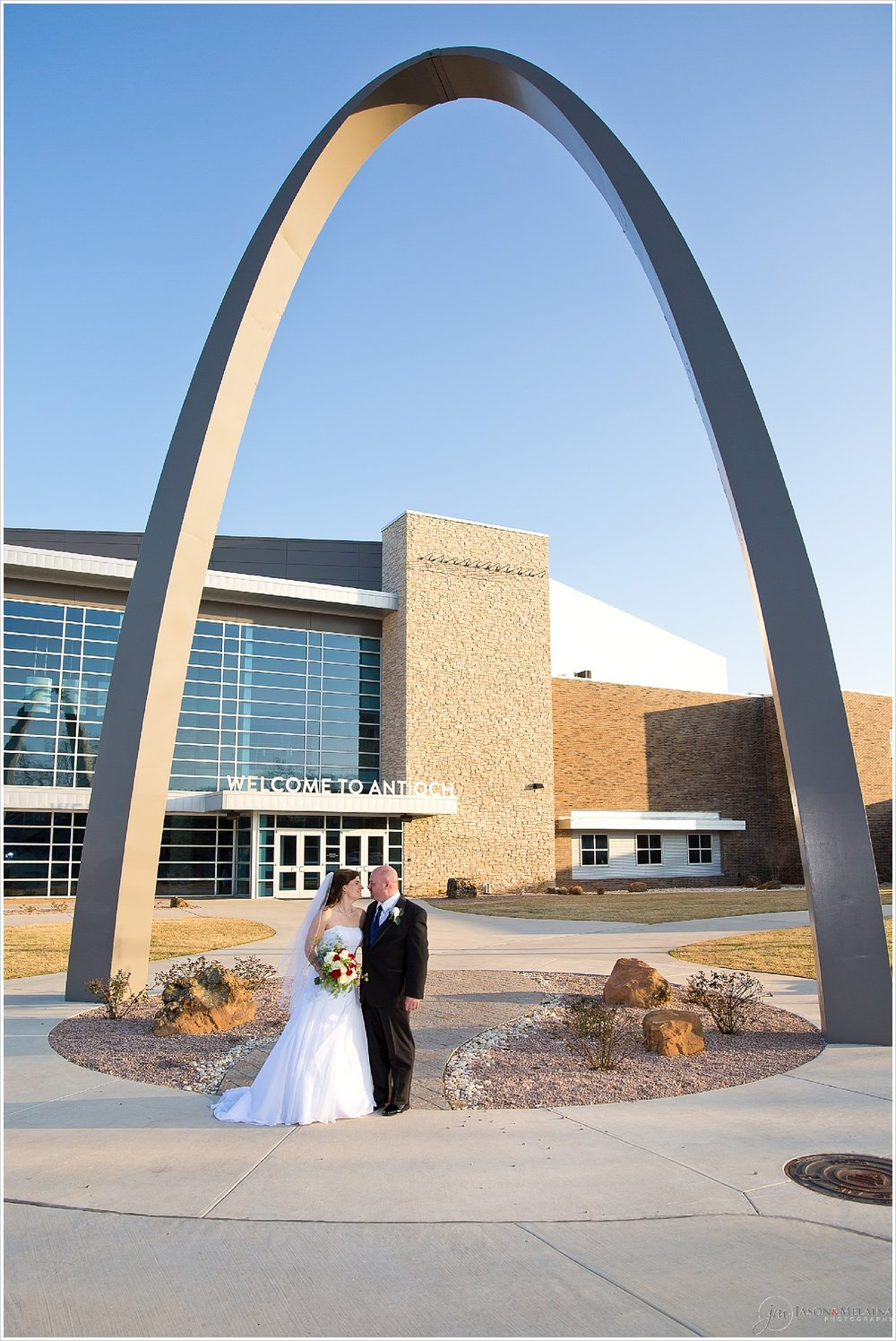 Bride and groom embrace under the arch outside Antioch Community Church in Waco, Texas