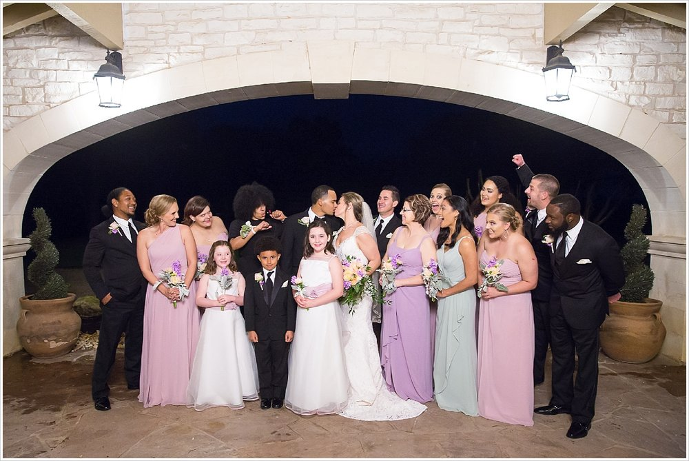 Bridal party cheers on as bride and groom kiss after wedding ceremony at La Rio Mansion