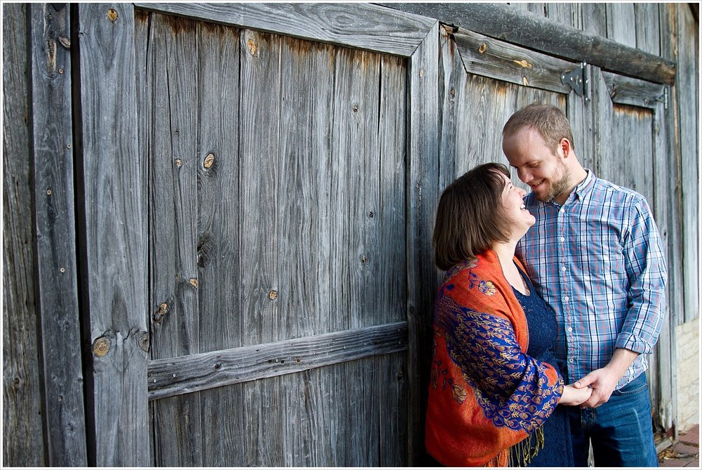 Couple embraces in front of rustic barn at Carleen Bright Arboretum in Woodway, Texas