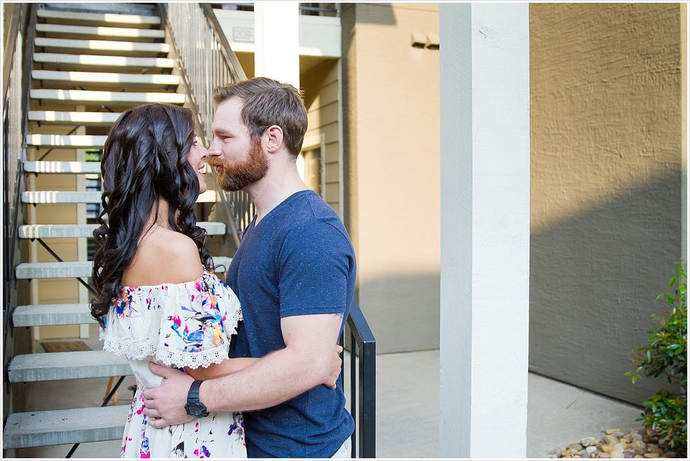 Randell and Fawn hold one another outside the apartment complex they met at during an engagement photography session in Frisco, Texas by Texas wedding photographers Jason & Melaina Photography, www.jasonandmelaina.com