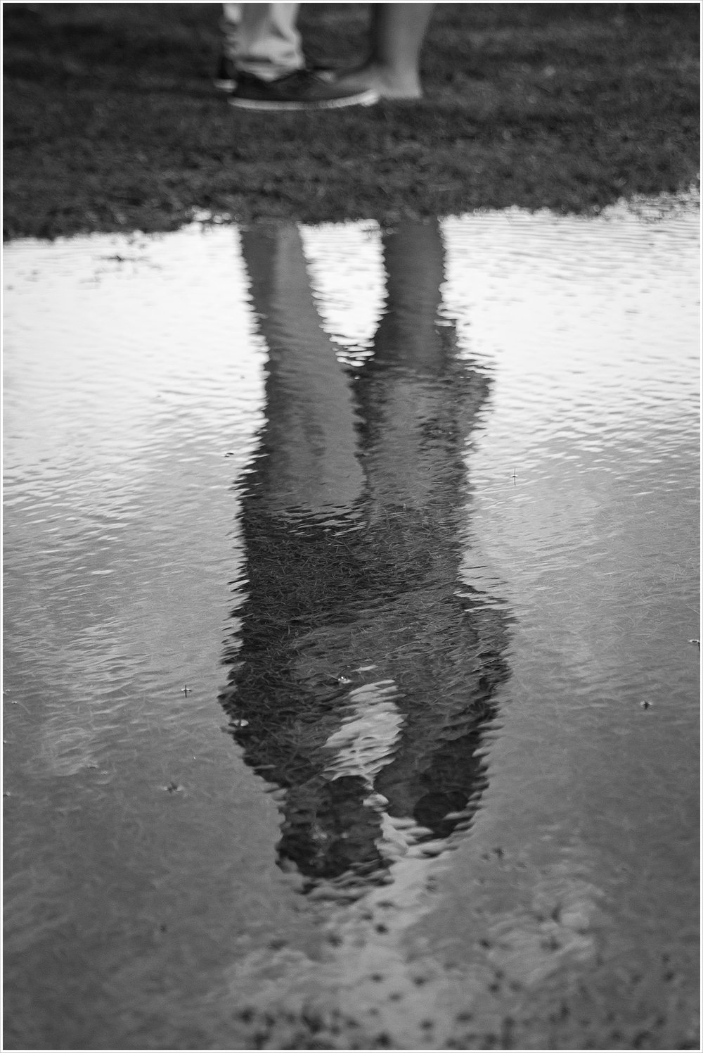 A black and white image of Randell and Fawn's reflection in water Randell & Fawn stand on a bridge in the park where Randell proposed at an engagement photography session in Frisco, Texas by Texas wedding photographers Jason & Melaina Photography, www.jasonandmelaina.com
