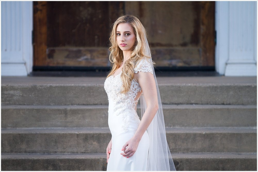 Model poses in gorgeous _______ wedding gown on the steps of Rapoport Academy in Waco, Texas. Photography by Jason & Melaina Photography, Texas wedding photographers. www.jasonandmelaina.com