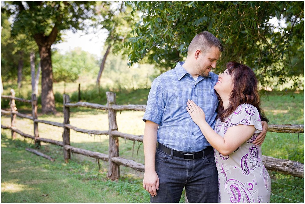 A couple smiles at one another during their engagement portraits at Brazos Bluffs Ranch in Waco, Texas - Jason & Melaina Photography, www.jasonandmelaina.com
