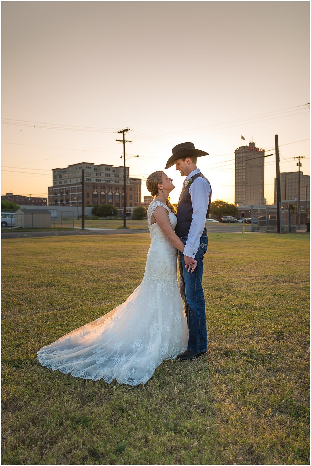 Bride and groom stand together with Waco skyline and sunset behind them, Navy and blush Texas Reception at The Phoenix Ballroom, Jason & Melaina Photography - www.jasonandmelaina.com