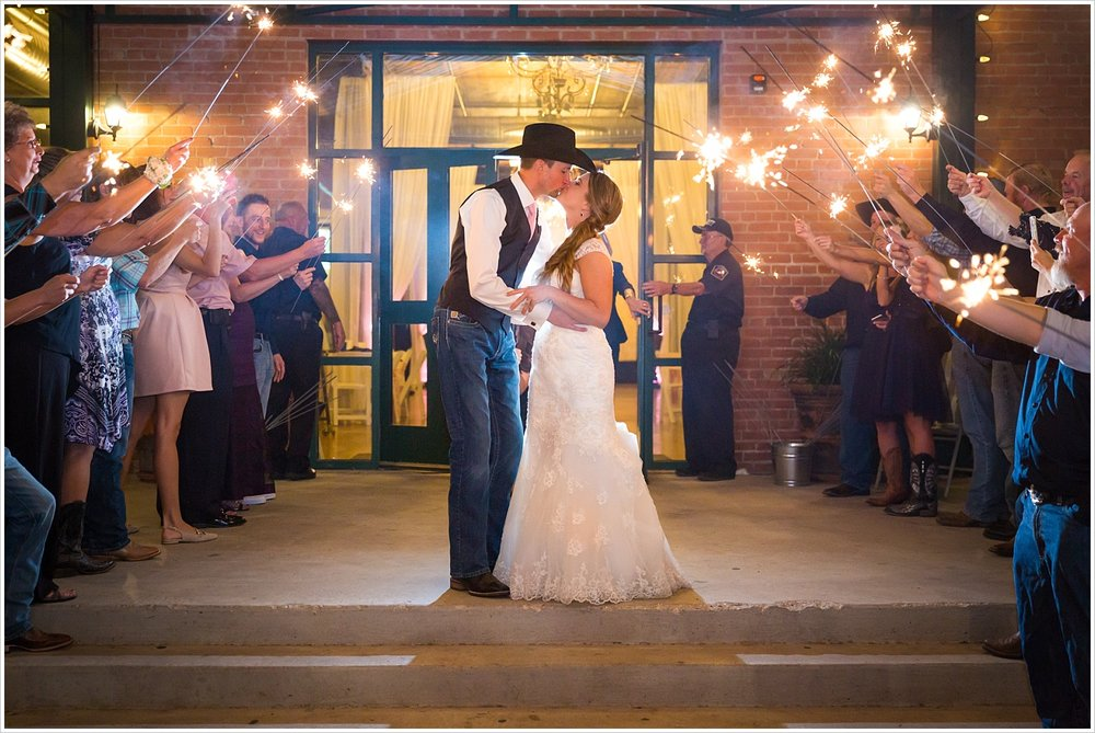 Bride and groom kiss during sparkler exit outside The Phoenix in Waco, Navy and blush Texas Reception at The Phoenix Ballroom, Jason & Melaina Photography - www.jasonandmelaina.com