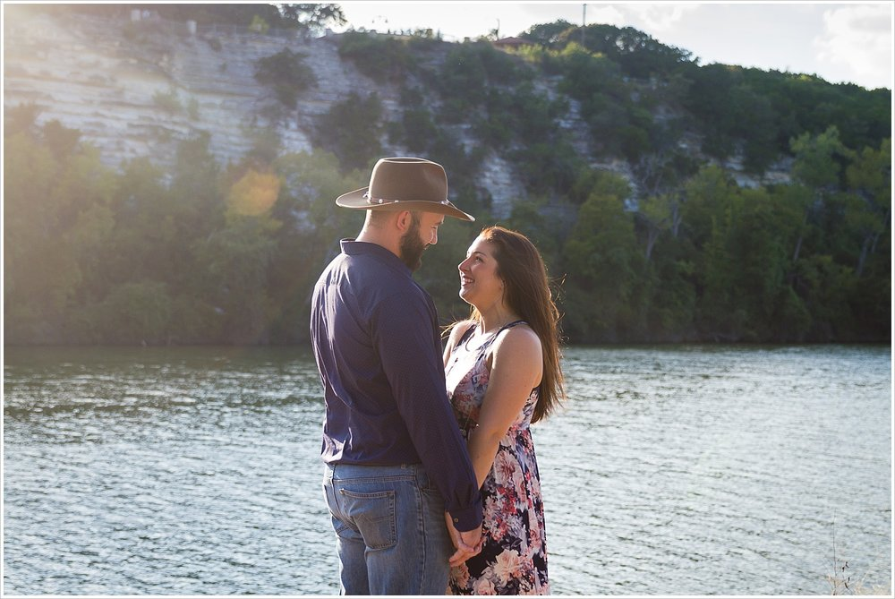 A couple stands close and smiles at one another by the Brazos River in their Waco, Texas engagement session, Jason & Melaina Photography, www.jasonandmelaina.com