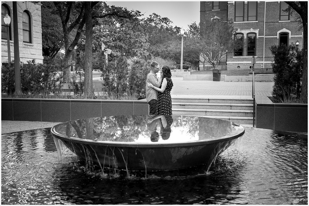 Couple embraces behind reflective fountain on Baylor University's campus - Jason & Melaina Photography - www.jasonandmelaina.com