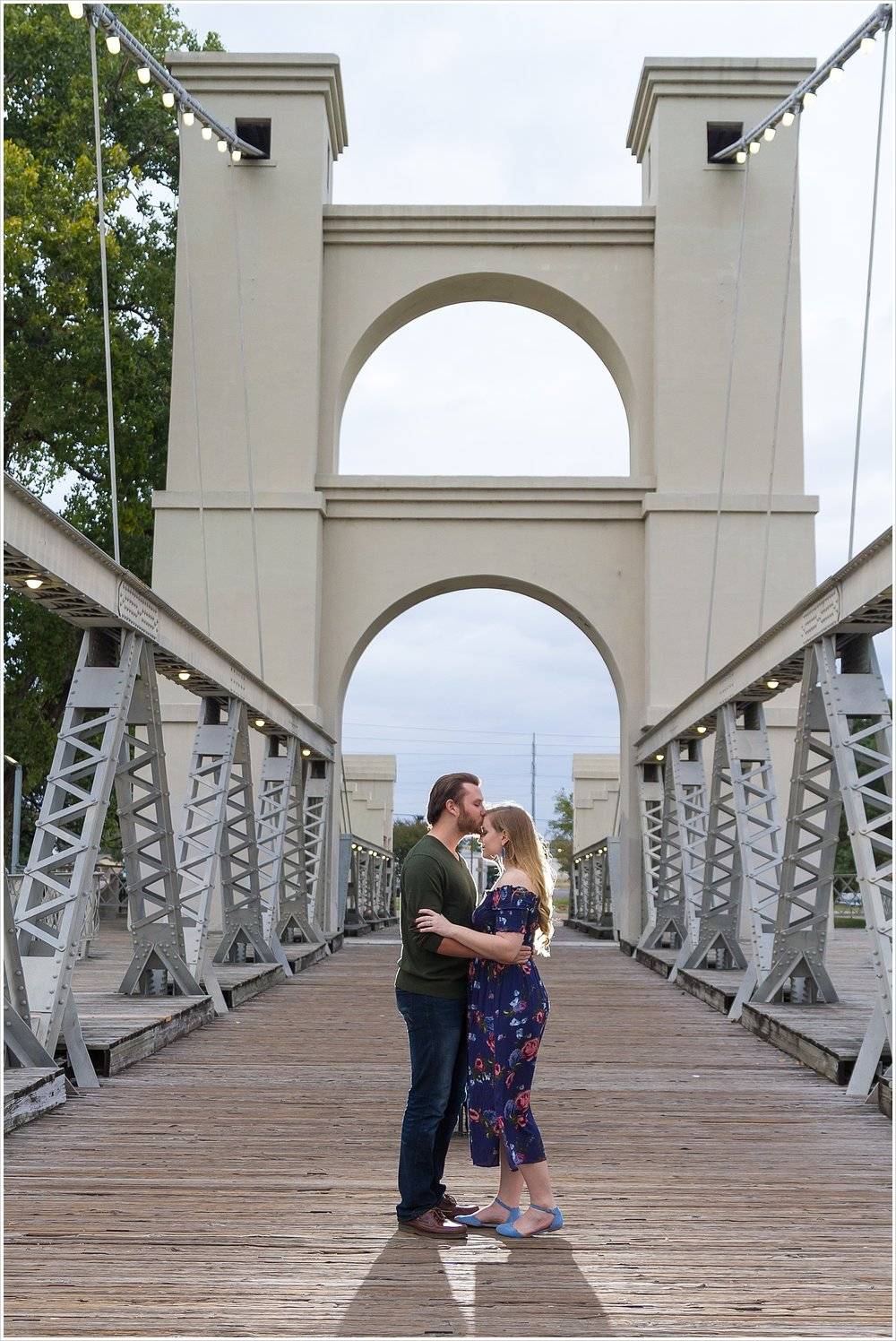 A man kisses his fiance's forehead as they embrace during their engagement photos on the Waco Suspension Bridge - Jason & Melaina Photography - www.jasonandmelaina.com
